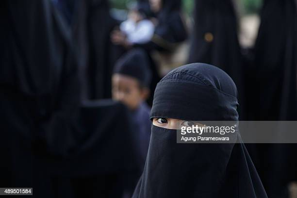A girl from the Islamic commune AnNadzir looks on as she attends Eid Al Adha mass prayer at Mawang Lake Gowa Regency on September 22 2015 in Makassar...