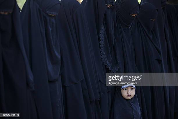 A girl from the Islamic commune AnNadzir looks on during Eid Al Adha mass prayer at Mawang Lake Gowa Regency on September 22 2015 in Makassar...