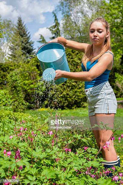 "girl gardening watering plants in a flower bed. - ""martine doucet"" or martinedoucet stock pictures, royalty-free photos & images"
