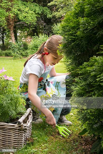 girl gardening, working with small rake - alexandra dost stock-fotos und bilder