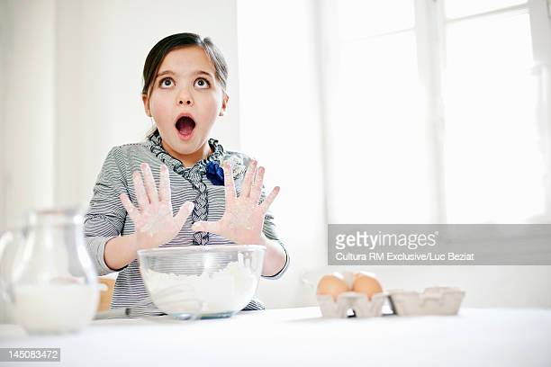 Girl gasping and baking in kitchen