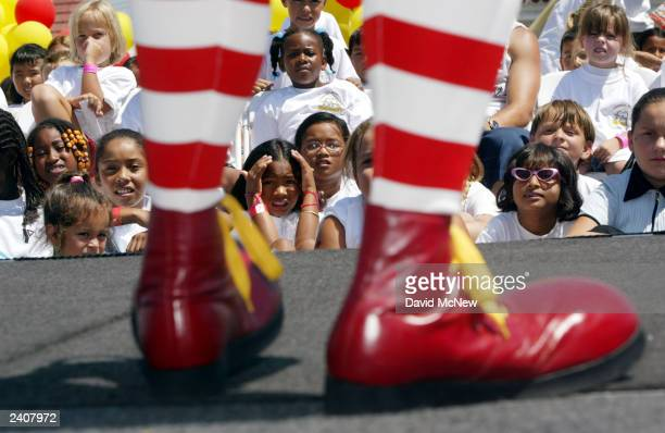 A girl gazes at the giant shoes of the Ronald McDonald mascot clown at the world's oldestoperating McDonald's fast food restaurant on its 50year...