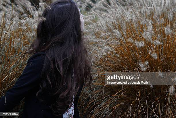 girl gazing over shoulder in bushes - rye new york stockfoto's en -beelden