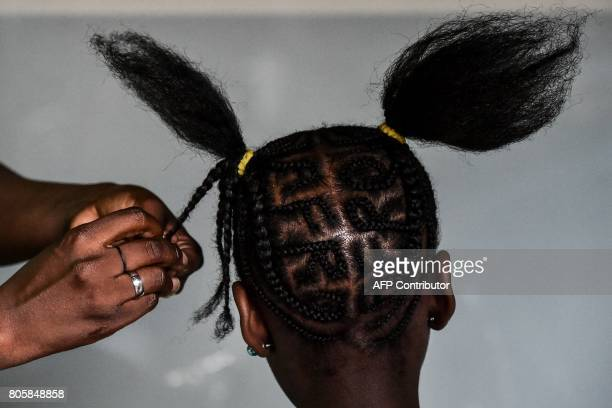 A girl gests an AfroColombian hairstyle during the 13th contest of Afro hairdressers Tejiendo Esperanzas in Cali Valle del Cauca department Colombia...