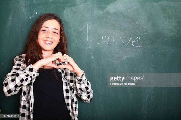 Girl gesturing heart shaped hands beside Love word on blackboard