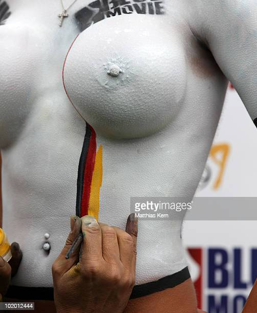 A girl gets a body painted football jersey of Germany during a sexy soccer match between VisitX Camgirls and Blue Movie All Stars at Traumstrand on...