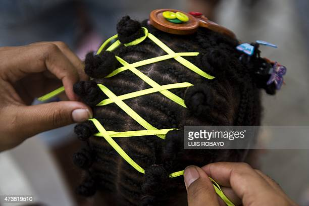 A girl gets an AfroColombian hairstyle done during the 11th Afrohairdressers contest Tejiendo Esperanzas on May 17 in Cali Valle del Cauca department...