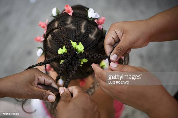 A girl gets an AfroColombian hairstyle during the 12th contest of Afro hairdressers Tejiendo Esperanzas in Cali Valle del Cauca department Colombia...