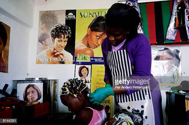A girl gets her hair done by a woman at the Beaulas Hair Saloon October 6 2003 in Khayelitsha the largest black township about 20 miles outside Cape...