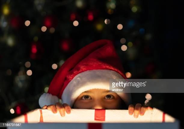 chica recibiendo un adelanto de un regalo de navidad - preestreno fotografías e imágenes de stock