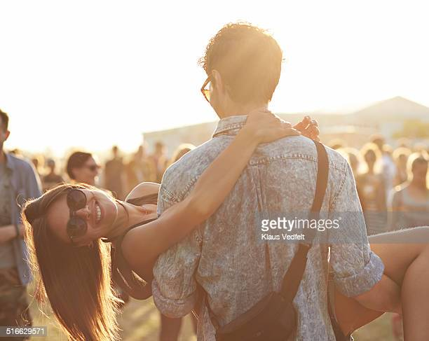 Girl getting carried by boyfrend at festival