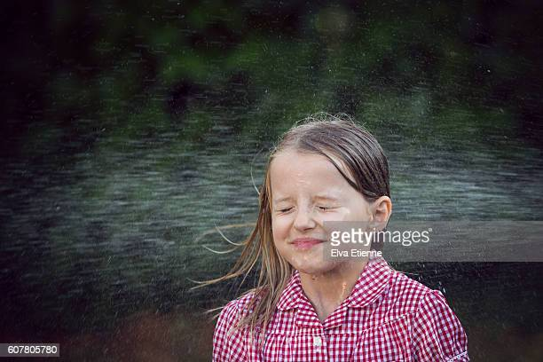 Girl (9-10) getting soaked by water spray