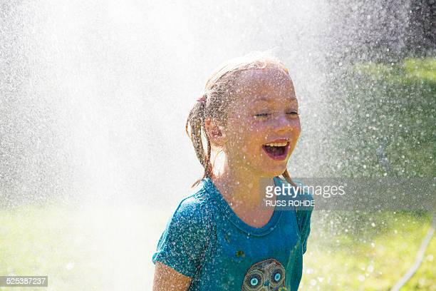 girl getting splashed by water sprinkler in garden - wet t shirt girls stock photos and pictures