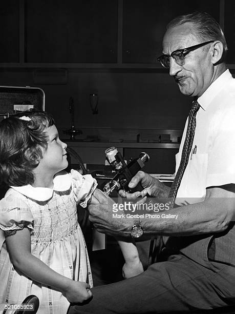 Girl getting vaccinated, late 1960s.