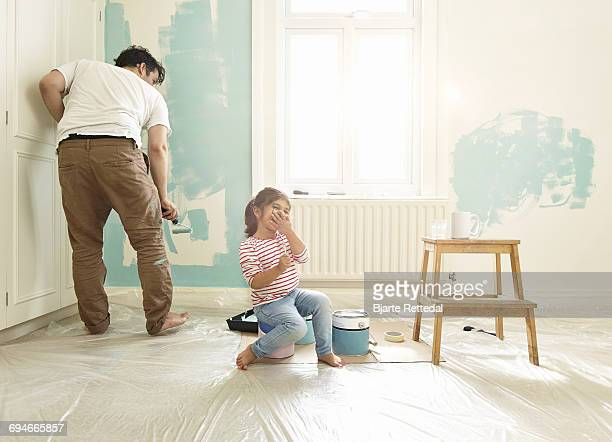 Girl giggling while dad paints