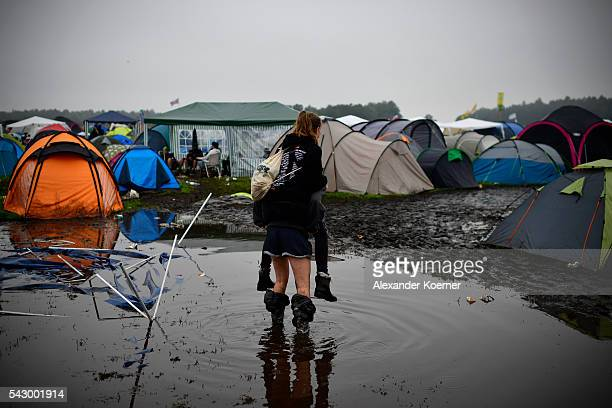 A girl gives another girl a piggyback ride through a puddle at the flooded camping compound at the Hurricane Festival compound on June 25 2016 in...