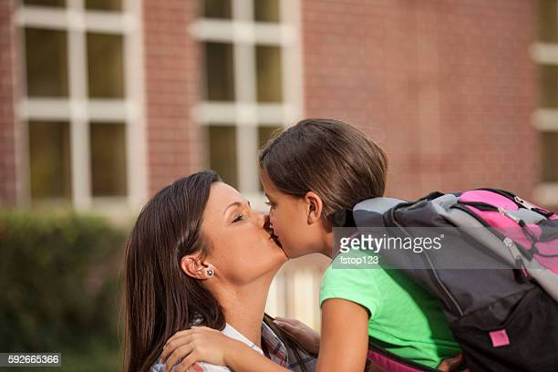 Girl gives mom goodbye kiss on first day of school.