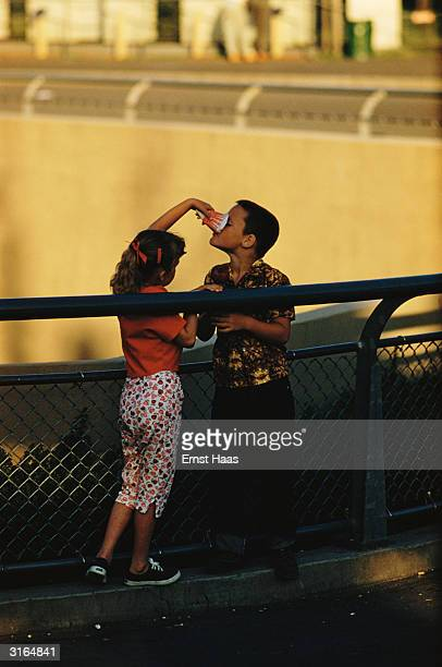 A girl giving a boy a drink from a paper cup circa 1965