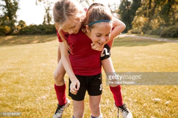 girl giving friend a piggyback ride in park - portare a cavalluccio foto e immagini stock