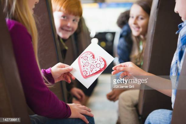 girl giving friend valentine on school bus - valentine card stock photos and pictures