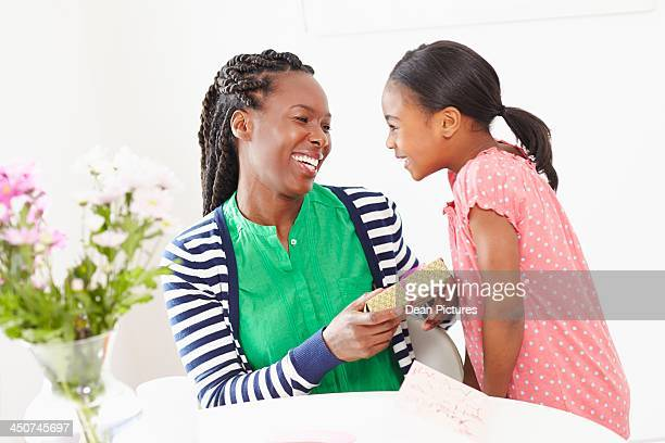 Girl (10-12) giving gift to mother