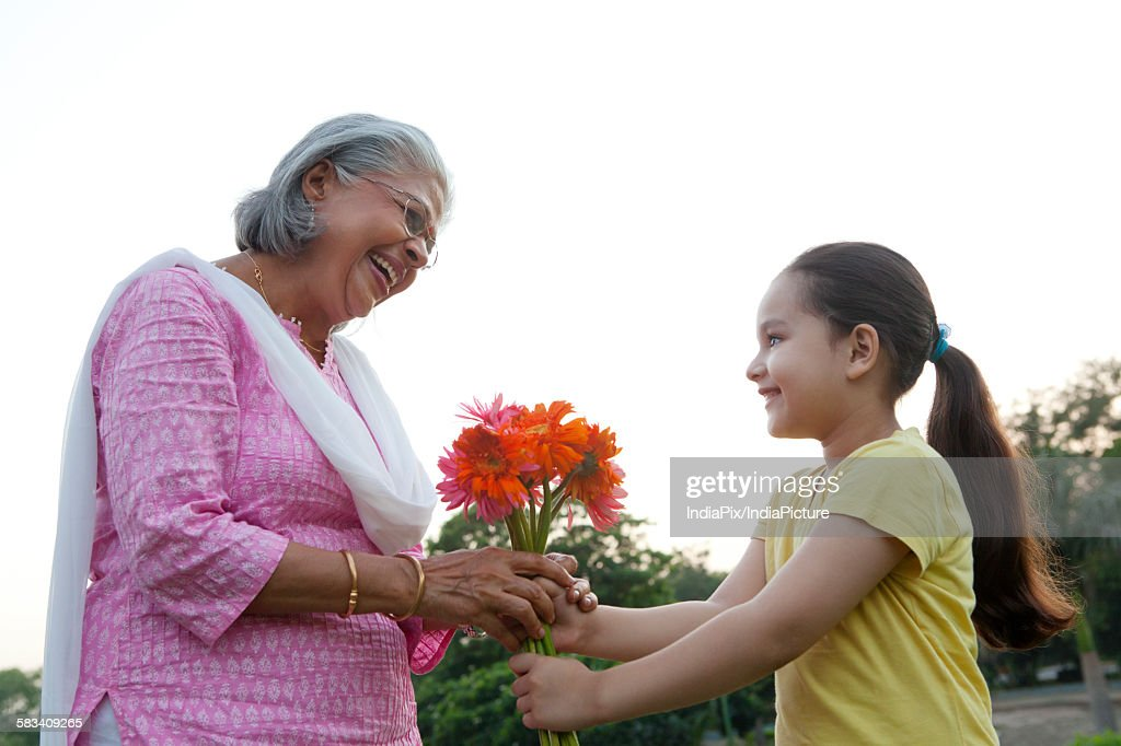 Girl giving her grandmother flowers : Stock Photo