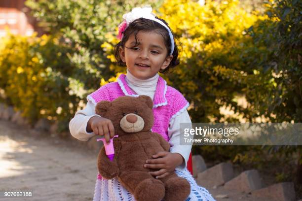 a girl giving injection to teddy bear - pakistan girl stock photos and pictures