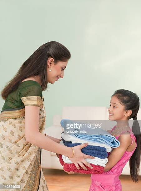 Girl giving ironed clothes to her mother