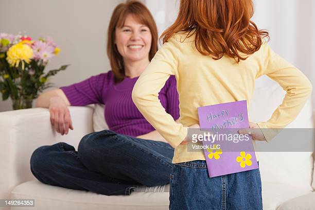 Girl (4-5) giving Mother's Day card to her mother