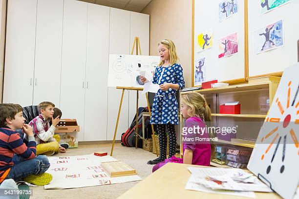 girl giving presentation to classmates - montessori education stock pictures, royalty-free photos & images