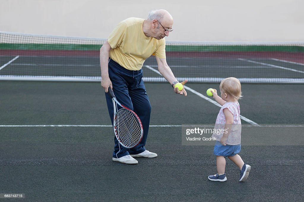 Girl giving tennis ball to grandfather while standing at playing field : Foto stock