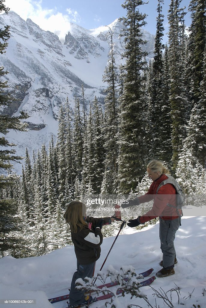 Girl (12-13) giving water bottle to mother, snowcapped mountains in background, high angle view : Stockfoto