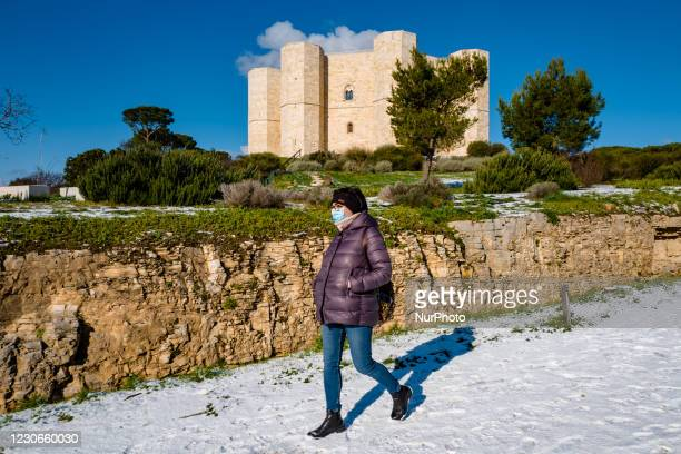 Girl goes down the road that leads to the Castel del Monte snow-covered by the snowfall of the night on January 18, 2021. The cold wave continues in...