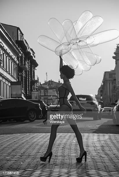 girl going down the street with balloons - zwart wit stockfoto's en -beelden
