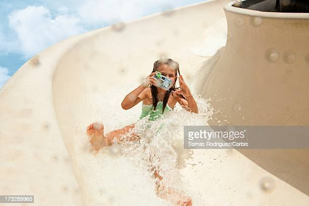 Girl (8-9) going down water slide holding toy camera