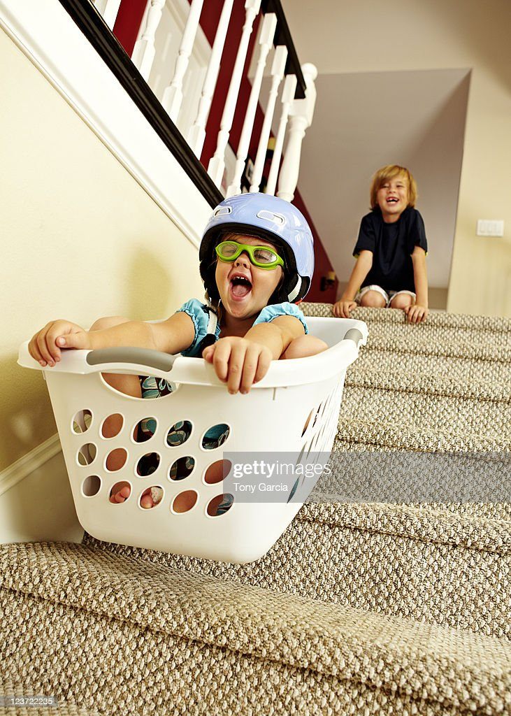Girl going downstairs in a laundry basket. : Stock Photo