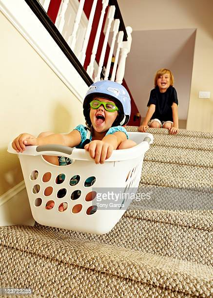Girl going downstairs in a laundry basket.