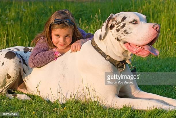 Girl & Great Dane dog laying on grass
