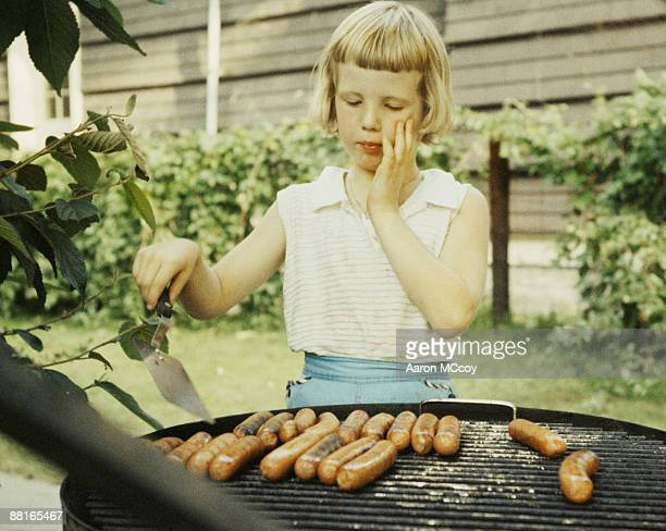 Girl grilling hot dogs