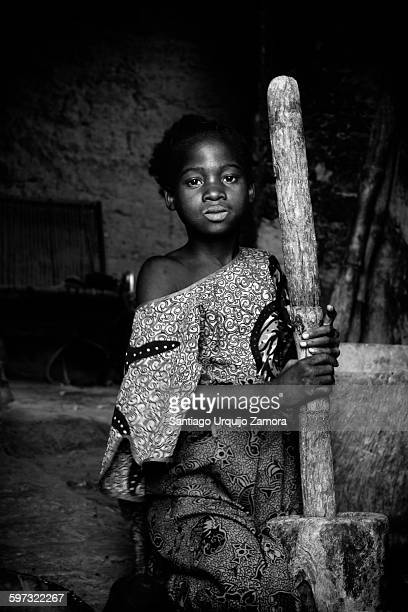 Girl grinding grain with a mortar and pestle, Sanga, Dogon Country, Mali