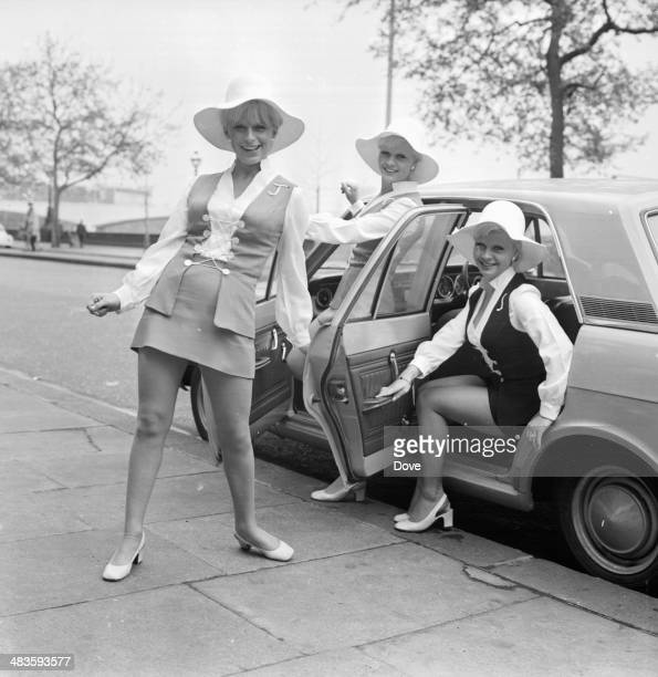 Girl group The Satin Bells posing next to a car whilst wearing large white hats 17th May 1968