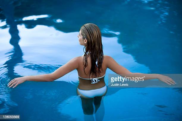 girl half in and half out of luxury pool water