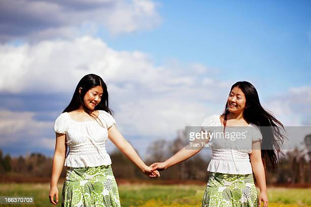 girl hand in hand in the sun - asian twins stock photos and pictures