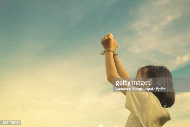 Girl Handcuffs Against Cloudy Sky