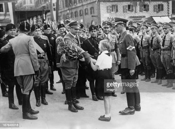 A BDM girl handes a bouquet to Rudolf Heß at his arrival in Roma In front of the train station October 28th 1937 Photograph Ein BDMMädchen überreicht...