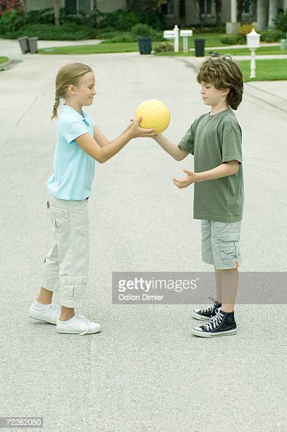 Girl handing boy ball in residential street