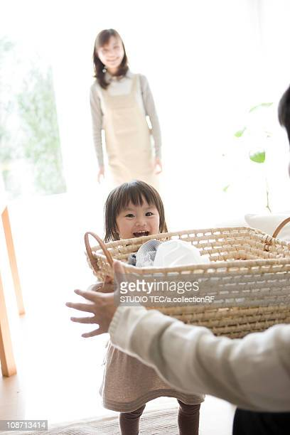Girl handing laundry basket to her Father