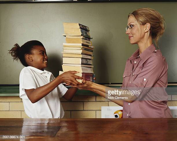 Girl (10-12) handing pile of books to woman in classroom