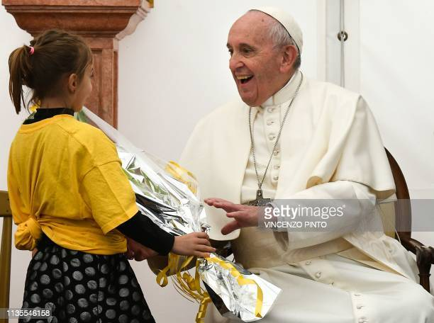 A girl hands a bouquet of flowers to Pope Francis during his pastoral visit to the San Giulio parish on April 7 2019 in Rome