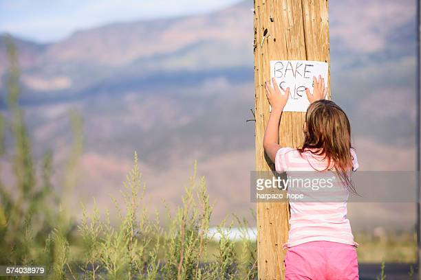 Girl hanging a bake sale sign